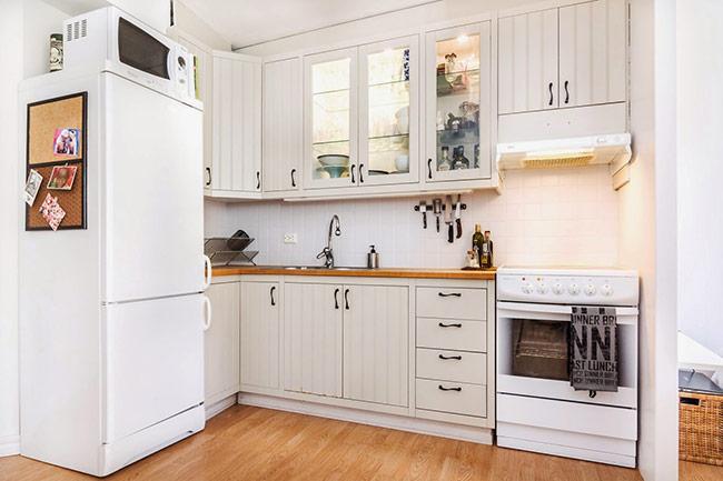 Căn bếp được trang trí đơn giản với tông màu trắng và gỗ, dù nhỏ nhắn nhưng căn bếp vẫn dư chỗ cho các dụng cụ nhà bếp.