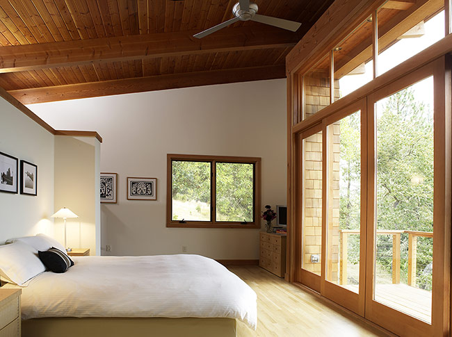Một phòng ngủ trên tầng áp mái không có lợi thế về diện tích nhưng lại có view khá đẹp. Chủ nhà đã biến căn phòng này thành nơi thư giãn tuyệt đối và tận dụng hết ưu điểm của phòng ngủ bằng hệ cửa kính kết hợp gỗ nhìn ra khu vườn xanh mát.