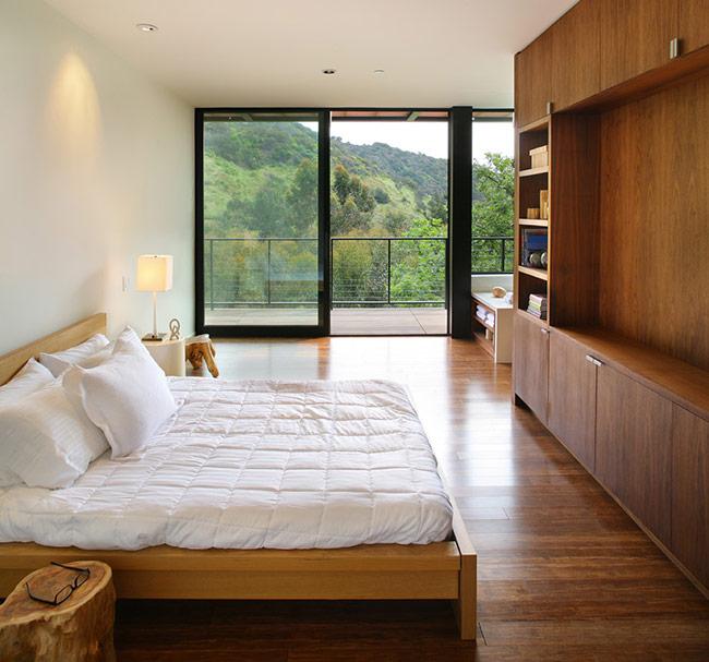 Việc sử dụng nội thất gỗ trong căn phòng này vô cùng hòa hợp với màu của thiên nhiên ngoài phòng ngủ. Chủ nhà đã sử dụng nội thất với thiết kế đơn giản nhất có thể để không lấn át vẻ đẹp phía ngoài cánh cửa.