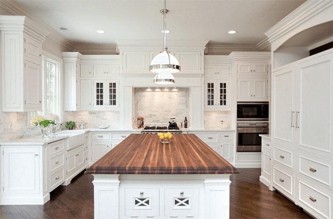 Sàn gỗ màu tro được ốp theo dạng chéo kết hợp thêm đảo bếp cũng bằng gỗ sự hài hòa nghệ thuật khi phối cùng với hệ thống tủ bếp và tường bếp màu trắng.