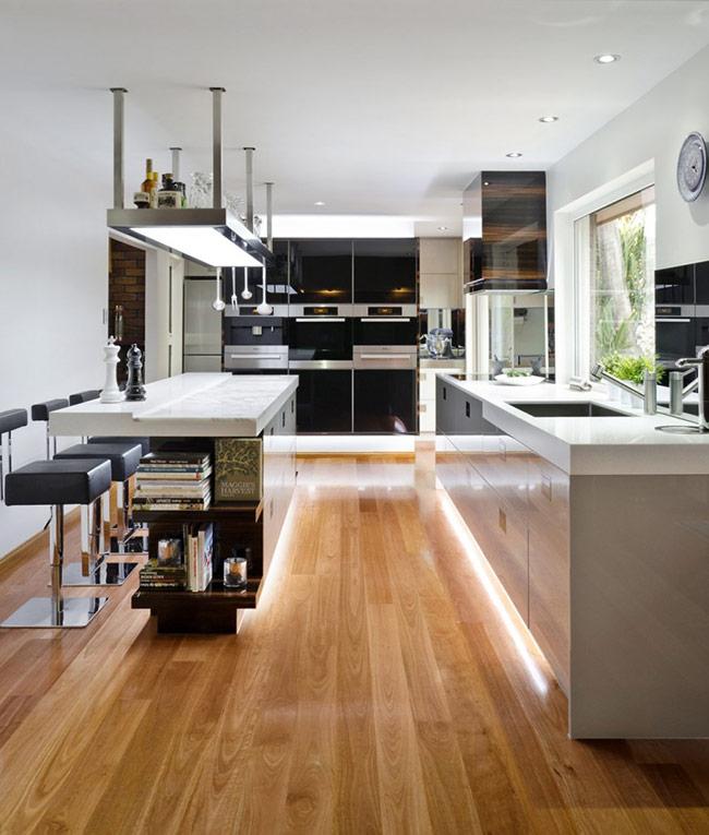 Sàn gỗ nâu vàng kết hợp thêm ánh sáng hắt ra quanh các khu vực đồ nội thất khiến không gian bếp này bừng sáng.