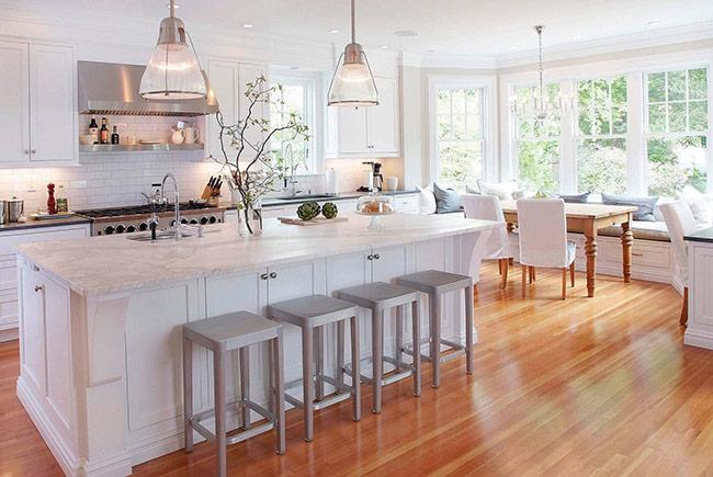 Phòng bếp này mang cả chút thanh lịch và chút nữ tính và có ánh sáng tuyệt đẹp, không chỉ nhờ ánh đèn, mà còn nhờ những chiếc tủ bếp hiện đại và đảo bếp màu trắng cũng như ánh sáng khi hắt vào sàn gỗ.