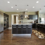 Có một chút hiện đại pha trộn lẫn trong thiết kế phòng bếp này, và điều này có được một phần là nhờ lựa chọn sàn gỗ màu tối – kết hợp với tủ gỗ màu đen sang trọng.