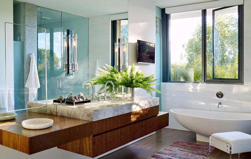 Đây là một ví dụ về cách một bồn tắm hình elip có thể biến phòng tắm trở nên duyên dáng. Nó có một tầm nhìn đẹp ra bên ngoài nhờ các cửa sổ lớn và vòi hoa sen mở trên bức tường đối diện giúp cho không gian tươi sáng hơn.