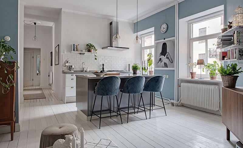 hòng khách và nhà bếp được tích hợp một cách cởi mở, và các bức tường được phủ một màu xanh da trời tươi mát và mềm mại.a